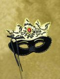 Carnival mask on a glitter background. Black and gold carnival mask on a glitter background , vertical image ideal for posters and copy space at top Royalty Free Stock Photography