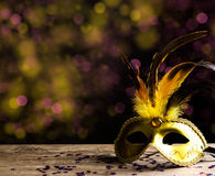 Carnival mask. Golden carnival mask on a wooden plate royalty free stock image