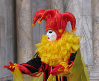 Carnival: mask, inviting. Carnival of Venice, Italy: Person wearing beautiful mask and costume in the colors red, yellow and black. Marble pillars in the Royalty Free Stock Photos