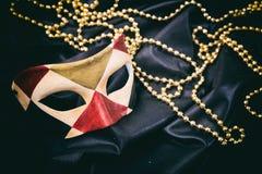 Carnival mask isolated on black satin background Stock Photos