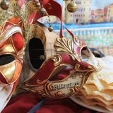 Carnival mask. With music notes somme pancakes and Venice in background and a other mask of jester Stock Image
