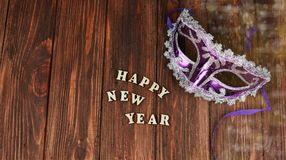Carnival mask for the new year. Purple on a wooden background Stock Photo