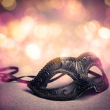 Black carnival mask. Carnival mask over gold background Stock Photos