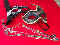 Carnival Mask and Pearl Necklace. Two carnival mask and pearl necklace on the red background Stock Images