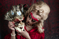 Carnival mask. Portrait of beautiful young girl with creative make up and big carnival mask in her hands, blonde hairstyle. Louis court intrigues. Red background Royalty Free Stock Photography
