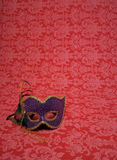 Carnival mask on red. Photo of a carnival mask on red decorative fabric that includes copy and cropping space stock photography