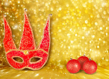 Carnival mask and a red Christmas ball Royalty Free Stock Photos