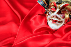 Carnival mask on red satin background. Harlequin carnival mask isolated on red satin background Royalty Free Stock Image