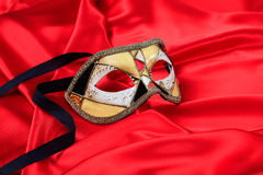 Carnival mask on red satin background. Carnival mask isolated on red satin background Royalty Free Stock Photography