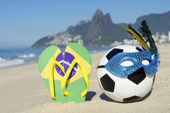 Carnival Mask Soccer Ball Football and Flip Flops on Beach Brazil. Soccer theme Rio Carnival football wearing sparkly mask with Brazil flag flip flops on Ipanema Royalty Free Stock Photography