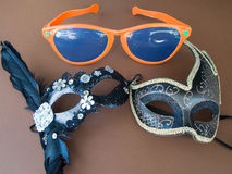 Carnival Mask and Sunglasses. Two carnival mask and orange sunglasses on the brown background Royalty Free Stock Photo
