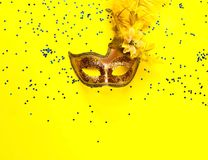 Carnival mask on yellow background with sparkles. Festive backdrop for projects. Flat lay, close up. stock image
