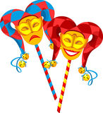 Carnival masks. Two masks on a stick in the comic and tragic hats with bells and ribbons Royalty Free Stock Images