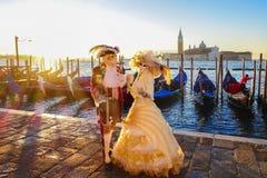Carnival masks against gondolas in Venice, Italy Stock Photos
