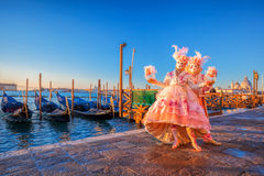 Carnival masks against gondolas in Venice, Italy Stock Images