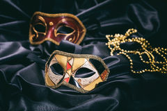 Carnival masks on black satin background Royalty Free Stock Image