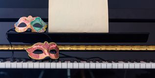 Carnival masks on piano keyboard, front view Stock Photography