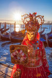 Carnival masks with mirror against gondolas in Venice, Italy Royalty Free Stock Photo