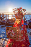 Carnival masks with mirror against gondolas in Venice, Italy Stock Image