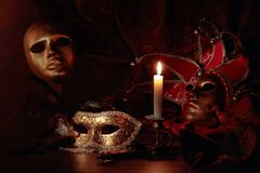 Carnival masks and small brass candlestick with burning candle. Carnival accessories on a old wooden table