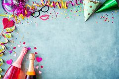 Carnival or New Years border background. With colorful streamers, party hats, confetti, accessories and two bottles of champagne on a textured blue grey stock photo