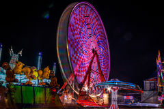 Carnival at night - rides in motion patterned lights. Carnival at night - rides in motion and bright blurred lights create fun entertainment for all ages Royalty Free Stock Photos