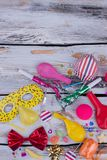 Carnival party background with colorful decorations. Birthday party items on wooden background, top view royalty free stock photo