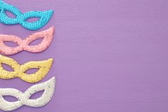 carnival party celebration concept with colorful pastel pink, gold, silver and blue masks over purple wooden background. Top view. royalty free stock photo