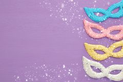 carnival party celebration concept with colorful pastel pink, gold, silver and blue masks over purple wooden background. Top view. stock photography