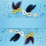 Carnival party celebration concept with elegant gold mask on stick over blue wooden background and stars. Top view. Carnival party celebration concept with royalty free stock image