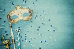 Carnival party celebration concept with elegant gold mask on stick over blue wooden background and stars. Top view. Carnival party celebration concept with stock photography