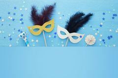 Carnival party celebration concept with elegant gold mask on stick over blue wooden background and stars. Top view. Carnival party celebration concept with stock images