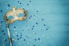 Carnival party celebration concept with elegant gold mask on stick over blue wooden background and stars. Top view. Carnival party celebration concept with stock photo