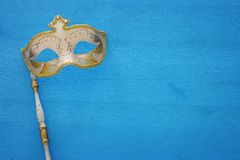 Carnival party celebration concept with elegant gold mask on stick over blue wooden background. Top view. Carnival party celebration concept with elegant gold royalty free stock photos