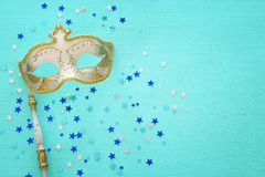 Carnival party celebration concept with elegant gold mask on stick over mint wooden background and stars. Top view. Carnival party celebration concept with stock photography
