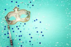 Carnival party celebration concept with elegant gold mask on stick over mint wooden background and stars. Top view. Carnival party celebration concept with royalty free stock photography