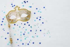 Carnival party celebration concept with elegant gold mask on stick over white wooden background and stars. Top view. Carnival party celebration concept with stock photo
