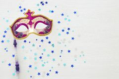 Carnival party celebration concept with elegant purple mask on stick over white wooden background and stars. Top view. Carnival party celebration concept with stock photo