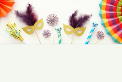 Carnival party celebration concept with gold and silver masks over white wooden background and colorful fans. Top view. Carnival party celebration concept with royalty free stock photo