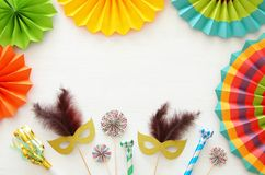 Carnival party celebration concept with gold and silver masks over white wooden background and colorful fans. Top view. Carnival party celebration concept with stock photo