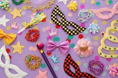Carnival party celebration concept with masks and colorful party accessories over pink, purple wooden background. Top view. Carnival party celebration concept royalty free stock photos