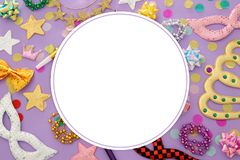 Carnival party celebration concept with masks and colorful party accessories over pink, purple wooden background. Top view. Carnival party celebration concept stock photos