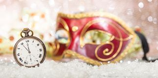 Carnival party countdown. Minutes to midnight on an old watch, venetian mask, bokeh festive background. Banner stock photos