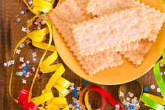 Carnival pastry. Carnival pastry with confetti on wooden table Royalty Free Stock Photography