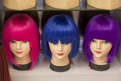 Colour carnival wigs. Carnival plastic wigs i shiny colours royalty free stock images