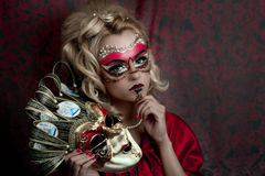 Carnival. Portrait of beautiful young girl with creative make up and big carnival mask in her hands, blonde hairstyle. Louis court intrigues. Red background Stock Images