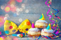Carnival donuts with paper streamers and party bow tie. Carnival powdered sugar raised donuts with paper streamers and party bow tie stock image
