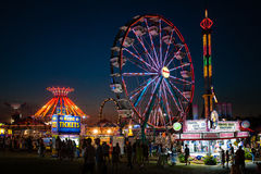 Carnival rides at night. Brightly lit carnival rides are a nighttime attraction at the Cecil County Fair in Maryland, USA. County fairs are an end of summer royalty free stock photo