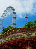 A Carnival Scene with the London Eye. A carnival scene with a carousel, the London Eye, and the United Kingdom and England flags waving in a blue sky stock photography