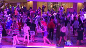 People singing and dancing to YMCA on a cruise ship. Includes audio.